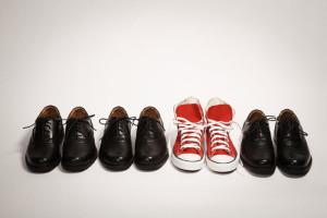Roter Schuhe zwischen schwarzen Schuhen